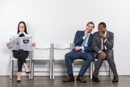 Photo for multiethnic businessmen gossiping and asian businesswoman reading newspaper while waiting for job interview - Royalty Free Image