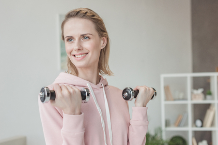 Photo pour Attractive smiling woman working out with dumbbells at home - image libre de droit