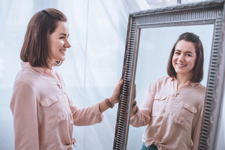 Photo pour Beautiful smiling young woman standing near mirror and looking at reflection - image libre de droit