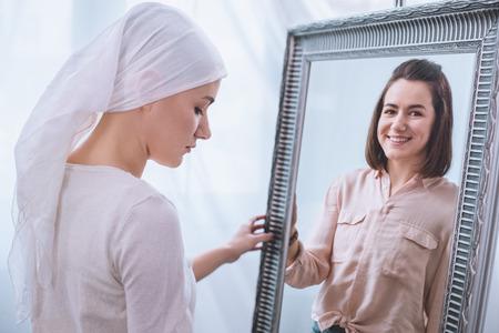 Photo pour Upset sick woman in kerchief standing near mirror with smiling reflection, cancer concept - image libre de droit