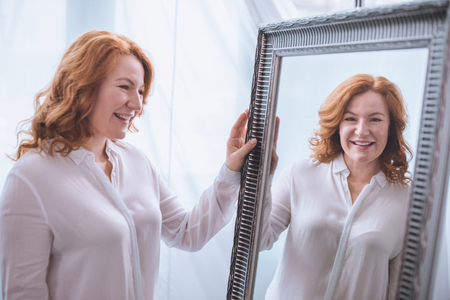 Photo pour beautiful smiling mature woman standing near mirror and looking at reflection - image libre de droit