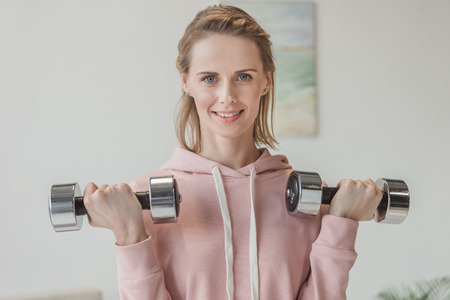 Photo pour Beautiful adult woman working out with dumbbells at home - image libre de droit