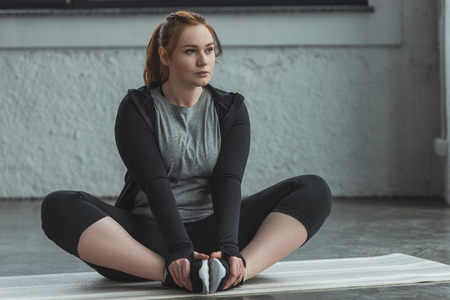 Photo pour Curvy girl stretching on floor in gym - image libre de droit
