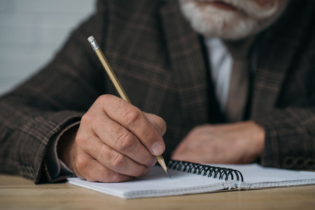 Photo pour Close-up shot of senior man writing in notebook with pencil - image libre de droit