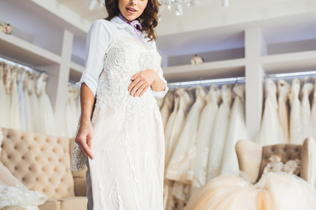 Photo pour Beautiful bride trying on dress in wedding atelier - image libre de droit