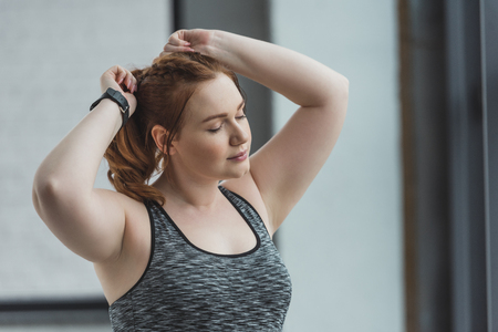 Photo pour Obese girl fixing her hair in gym - image libre de droit