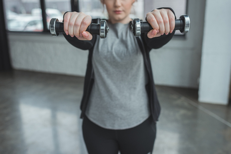 Photo pour Obese girl exercising with dumbbells in gym - image libre de droit