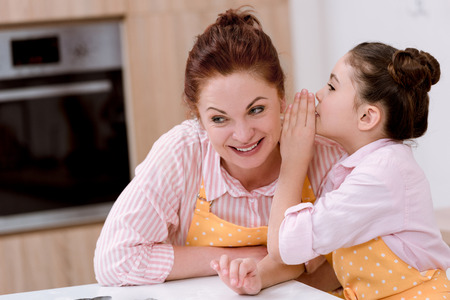 Photo for Grandmother gossiping with little granddaughter while cooking - Royalty Free Image