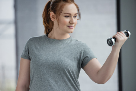 Foto de Curvy girl training with dumbbell in gym - Imagen libre de derechos