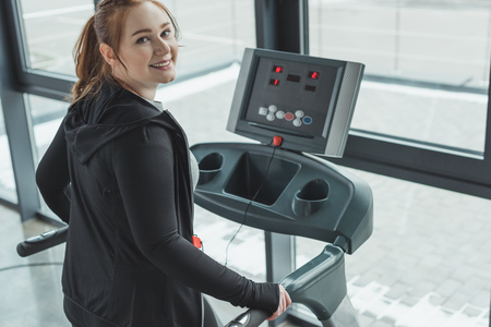 Photo pour Curvy girl smiling while on treadmill in gym - image libre de droit