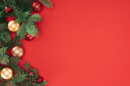 Foto de flat lay with pine tree branches with red and golden christmas balls isolated on red - Imagen libre de derechos