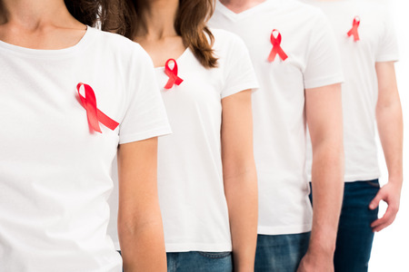 Photo pour Cropped image of people standing with red ribbons on shirts isolated on white background, world aids day concept - image libre de droit