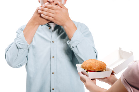 Photo pour cropped image of man covering mouth, woman proposing burger isolated on white - image libre de droit