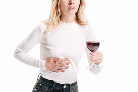 Foto de cropped image of woman showing liver pain and holding glass of red wine isolated on white - Imagen libre de derechos
