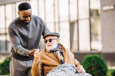 Foto de African american man giving joint to senior disabled man in wheelchair while they spending time together on street - Imagen libre de derechos