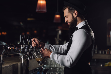Photo pour side view of bartender pouring beer from beer taps into glass - image libre de droit