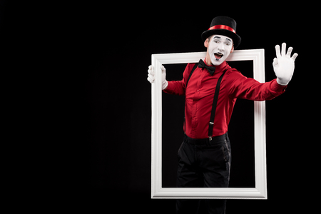 Photo pour happy mime waving hand from frame isolated on black - image libre de droit