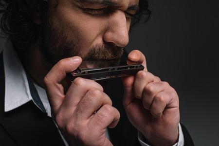 Foto de close-up portrait of expressive musician playing harmonica on black - Imagen libre de derechos