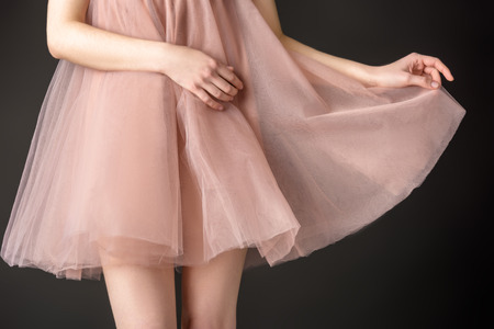 Photo for cropped view of tender girl posing in pink chiffon dress, isolated on grey - Royalty Free Image