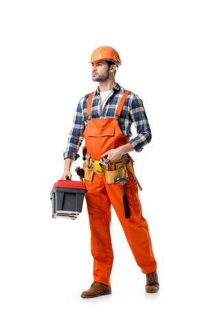Foto de Young confident repairman in orange overall holding tool box isolated on white - Imagen libre de derechos
