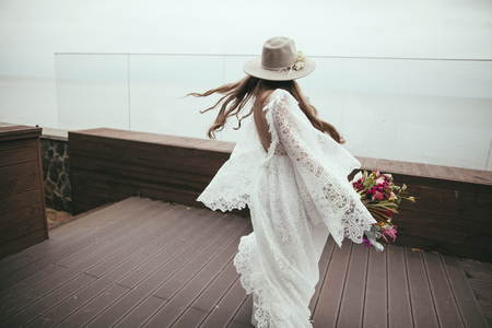Foto de beautiful bride in bohemian wedding dress and hat with bouquet - Imagen libre de derechos