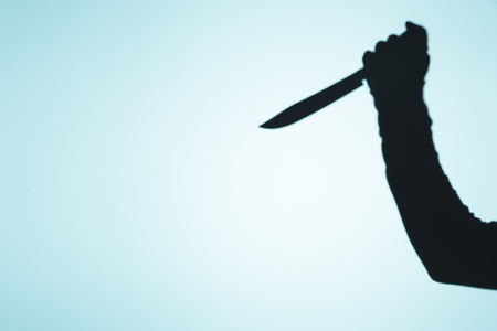 Photo for spooky shadow of person holding knife in hand on blue - Royalty Free Image