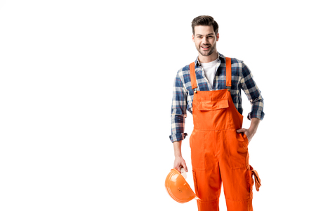 Foto de Smiling handyman in orange overall holding hard hat isolated on white - Imagen libre de derechos