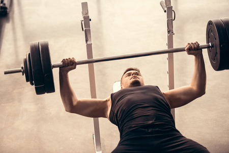 Foto de handsome sportsman lifting barbell on bench press in gym - Imagen libre de derechos