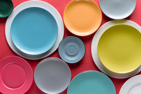 Photo pour Stacks of colorful porcelain plates on red background - image libre de droit