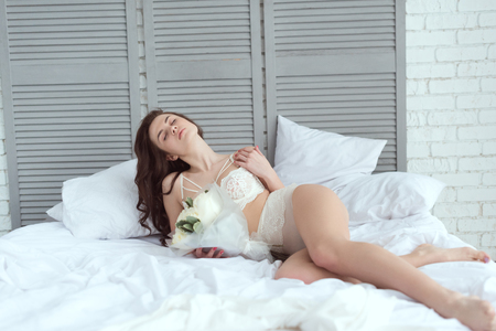 Foto de sexy woman in white underwear with bouquet of roses resting on bed - Imagen libre de derechos