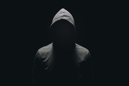 Foto de faceless man in hoodie standing isolated on black - Imagen libre de derechos