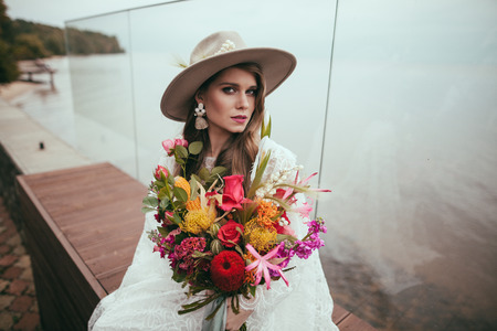 Foto de attractive bride in bohemian wedding dress and hat with bouquet - Imagen libre de derechos