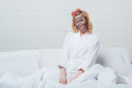 Photo pour beautiful woman in bath robe with facial mask sitting in bed - image libre de droit