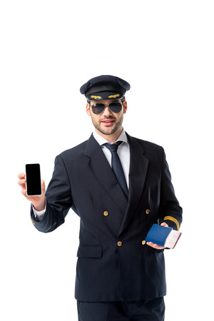 Foto de portrait of pilot in uniform with passport and ticket in hand showing smartphone with blank screen isolated on white - Imagen libre de derechos
