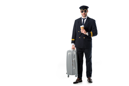 Photo pour young pilot in uniform and sunglasses with coffee to go and luggage isolated on white - image libre de droit