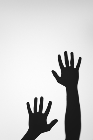 Photo for scary mysterious shadows of human hands on grey - Royalty Free Image