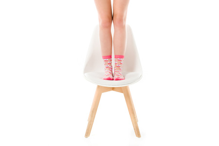 Photo for Female legs in pink socks standing on chair isolated on white - Royalty Free Image