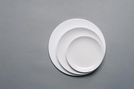 Photo pour White plates of different sizes on grey background - image libre de droit