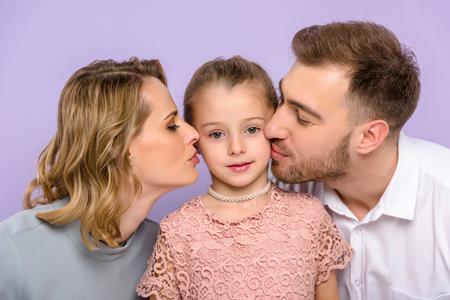 Photo pour Parents kissing daughter isolated on violet - image libre de droit