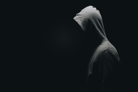 Foto de side view of unrecognizable man in man standing isolated on black - Imagen libre de derechos