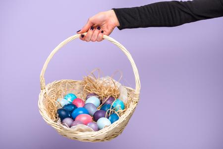 Foto de Woman holding Easter basket with colored eggs isolated on violet - Imagen libre de derechos