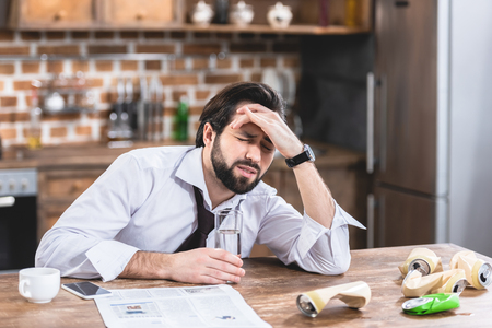 Foto de loner businessman having headache and hangover at kitchen - Imagen libre de derechos