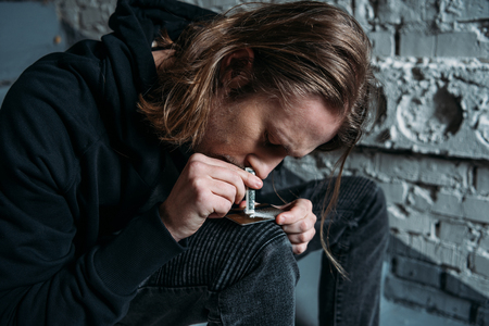 Foto de close-up shot of addicted man sniffing cocaine from credit card - Imagen libre de derechos