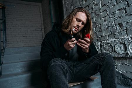 Foto de young man smoking cigarette while sitting on stairs - Imagen libre de derechos