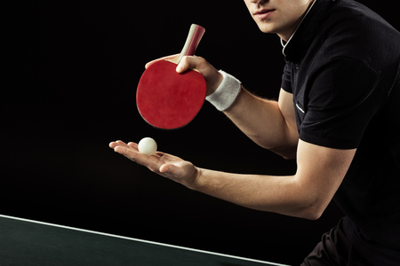 Foto de cropped shot of tennis player with tennis ball and racket in hands isolated on black - Imagen libre de derechos
