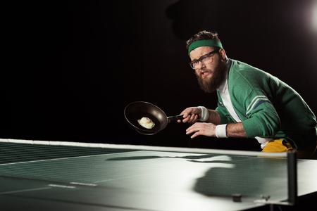 Photo pour tennis player with frying pan with egg playing table tennis isolated on black - image libre de droit