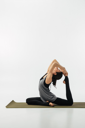 Foto de woman practicing yoga and doing king pigeon isolated on white - Imagen libre de derechos