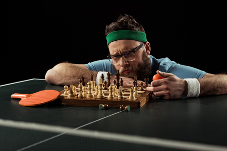 Photo pour pensive bearded man looking at chess board on tennis table isolated on black - image libre de droit