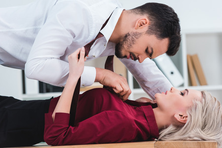 Photo pour side view of businessman unbuttoning shirt of young businesswoman at workplace - image libre de droit