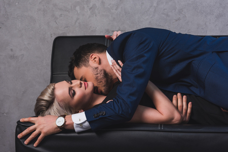 Photo pour side view of sexy young couple kissing on couch - image libre de droit